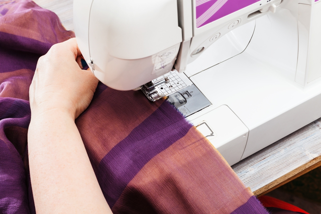 City homesteading sewing fabric on a sewing machine